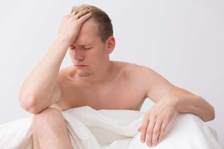 carelessness: Young guy is sitting in bed and holding his head