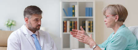 doctor stress: Elderly woman is explaining her problems to a concerned therapist