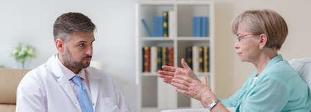 medico con paciente: La mujer mayor está explicando sus problemas con un terapeuta que se trate Foto de archivo