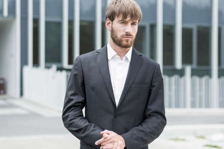 solemn: Man outside company is standing with solemn expression Stock Photo