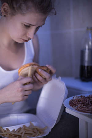 obsessed: Image of ill and unhappy woman obsessed with food Stock Photo