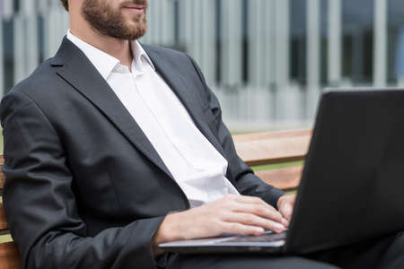 man close up: Man is working on computer outside of company Stock Photo