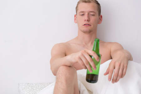 get tired: Young guy is drinking in bed Stock Photo