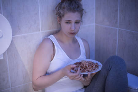 overeat: Picture of overeating sad girl sitting in bathroom