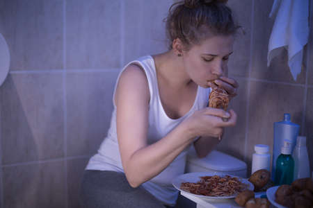 Photo of girl with bulimia can not control her hunger Stock Photo