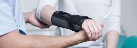 安定剤で脱臼の手首を持つ女性は、医師に相談します。 写真素材