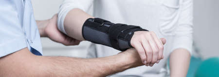 contusion: Woman with dislocated wrist in stabilizer is consulting doctor