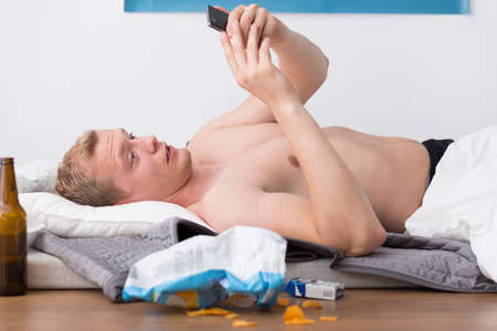 passed out: Young guy is looking at pictures from last night telephone Stock Photo