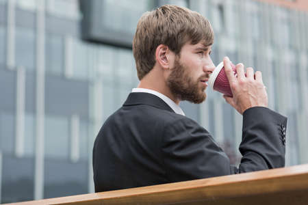 guys: Young businessman sitting on a bench and drinking beverage Stock Photo
