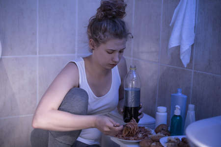 overeat: Photo of sick and sad young female eating unhealthy Stock Photo
