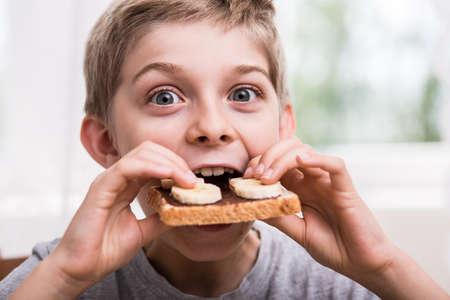 comiendo frutas: Muchacho que come tostadas con chocolate y plátano