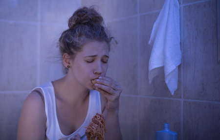 bulimia: Image of overeating teenage bulimic ashamed of her problem