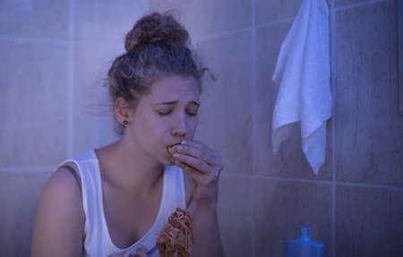 Image of overeating teenage bulimic ashamed of her problem
