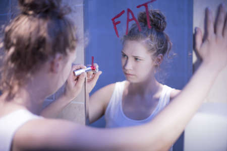 on mirrors: Image of slim frustrated girl thinking she is fat