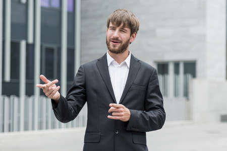 ambitious: Young ambitious businessman is showing something outside company