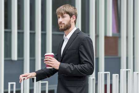 pensiveness: Young man in suit is holding cup of coffee Stock Photo