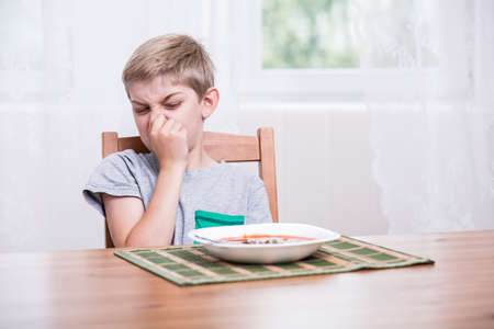 fussy: Child sitting at the table and refusing to eat soup
