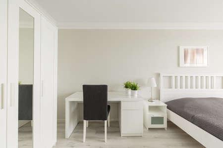 recreation room: Photo of light cosy bedroom with study area Stock Photo