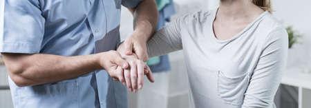 Mannelijk fysiotherapeut masseert vrouwelijke patiënt de hand Stockfoto
