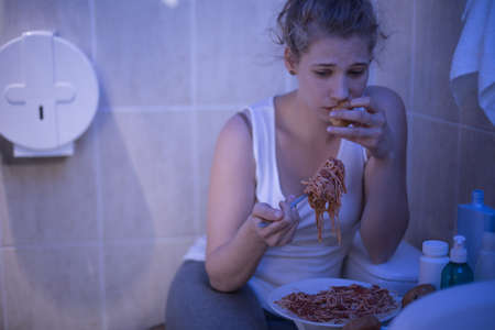 fat girl: Image of depressed girl eating out of control Stock Photo