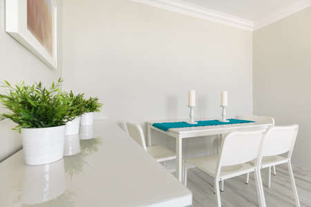 dining table and chairs: Image of white wooden cabinet and dining table with chairs Stock Photo