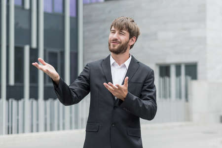 Man is gesticulating while describing plans for company development Imagens