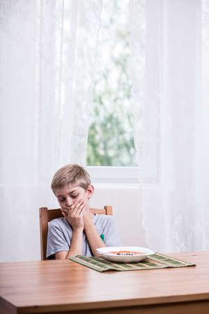 refusing: Picky boy refusing to eat tomato soup