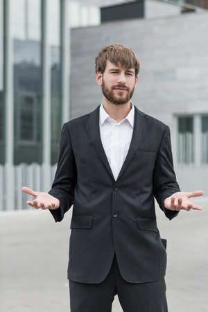 gesticulating: Attractive man is standing outside and gesticulating