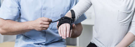 Mannelijke fysiotherapeut zet stabilisator op patiënthand