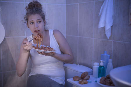 Picture of female ashamed of her illness eating in bathroom