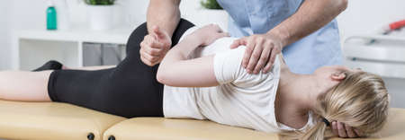 laying on back: Physiotherapist is rehabilitating young woman back in medical office