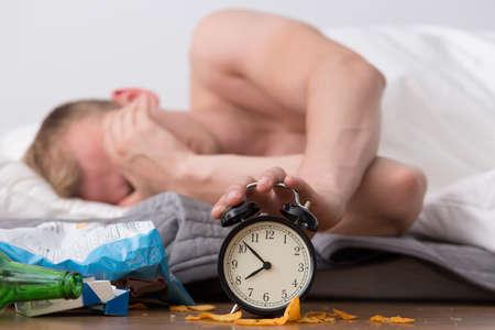二日酔いの男が目を覚ます、アラームを止める 写真素材