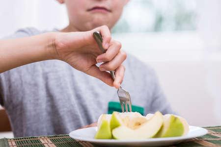 displeasure: Close-up of displeased boy eating healthy apple