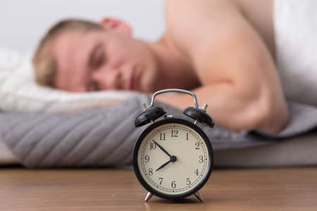 overslept: Man is asleep and does not hear the alarm clock Stock Photo