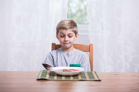トマトのスープのプレートを持った少年 写真素材
