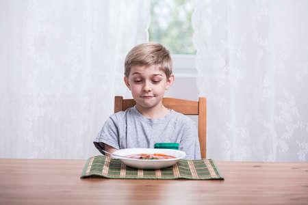 hungry children: Little boy with plate of tomato soup Stock Photo