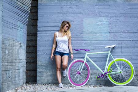 スポーティな女の子と彼女のトレンディなカラフルなバイクの写真