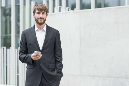 business man phone: Young man in business suit is holding his phone