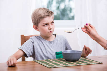 eater: Poor eater refusing to eat milk with cereal Stock Photo