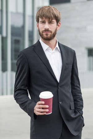 standing businessman: Young businessman in suit standing with coffee