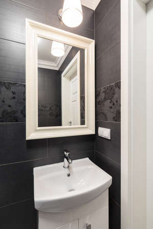 tiling: Photo of washbasin and mirror with black tiling in backgground