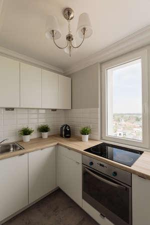 新しい白いデザインのキッチン シャンデリア付きの写真