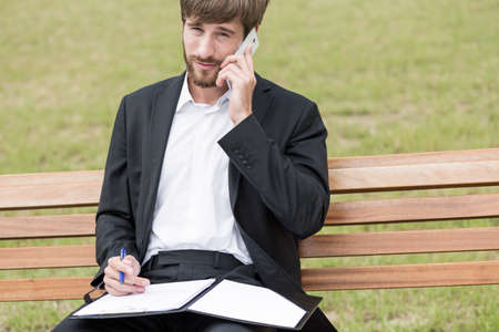 filling out: Man is talking on the phone and filling out documents
