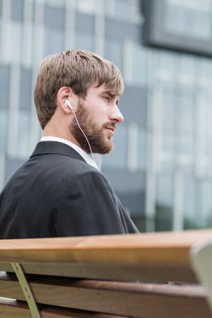 work suit: Young man is sitting on a bench and listening music
