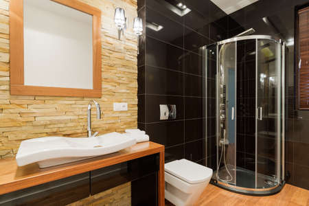 Extravagant decor of new bathroom with black tiles Imagens