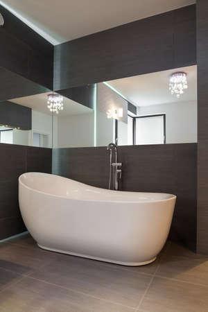 넓은 갈색 욕실에서 멋진 모양의 흰색 목욕