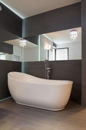 White bath in fancy shape in spacious brown bathroom