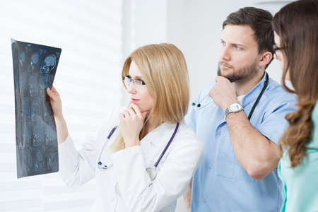 physicians: Two young afraid physicians checking patients head scanning Stock Photo