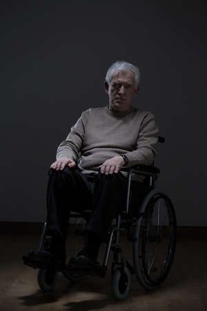 Lonely disabled senior man sitting in a wheelchair