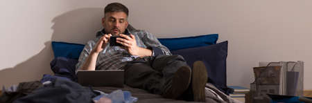 untidy text: Lazy adult man lying on the bed Stock Photo